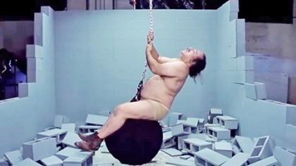 """El actor porno Ron Jeremy realizó una parodia del video """"Wrecking Ball"""" de Miley Cyrus, en el que él mismo interpreta la canción y, al igual que Cyrus, se balancea en una bola de demolición. Ron Jeremy, de 60 años, tiene una larga trayectoria como actor porno, ha participado en más de 2 mil películas para adultos."""