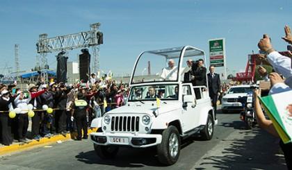 """Miles de católicos que se trasladaron a Ecatepec para ver pasar el """"papamóvil"""" que transporta al Santo Padre, celebraron haberlo visto aunque sea unos segundos."""